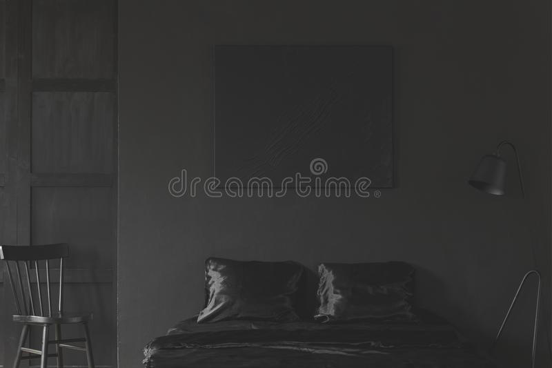 Mockup of black empty poster above bed in dark bedroom interior stock photography
