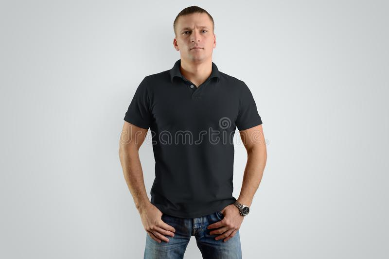 Mockup black polo shirts. Athletic man is isolated on a gray b. Mockup black polo shirts. A young athletic man is isolated on a gray background. Template can be stock images