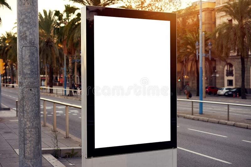Mockup of a blank empty white advertising urban billboard, placeholder template city street, space for design layout, sunset light.  royalty free stock image