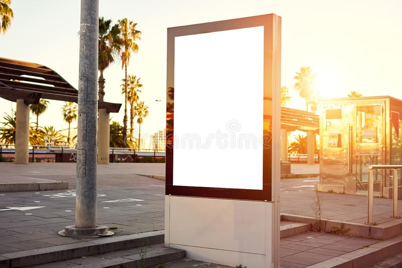 Mockup of a blank empty white advertising urban billboard, placeholder template city street, space for design layout, sunset light.  royalty free stock images