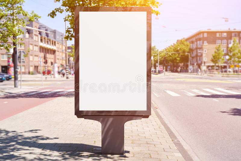 Mockup of a blank empty white advertising urban billboard, placeholder template city street, space for design layout, sunset light.  royalty free stock photography