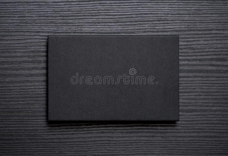Mockup of blank textured black business card on dark wood background.  royalty free stock photography