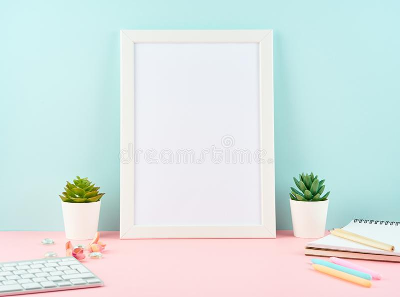 Mockup with blank white frame, alarm, notepad, keyboard on pink table against blue wall with copy space. Modern bright office. Desktop royalty free stock image