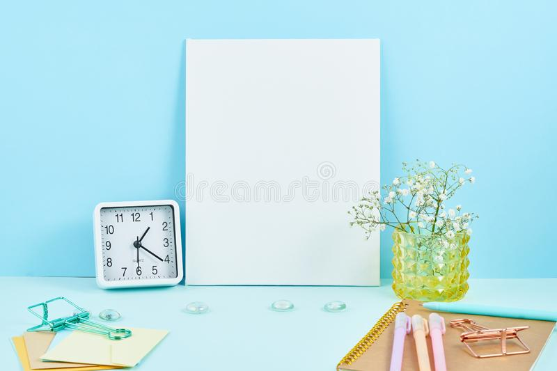 Mockup with blank white frame on blue table against blue wall, alarm, flower in vaze stock photos