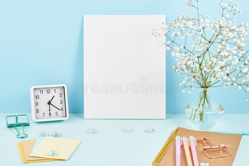 Mockup with blank white frame on blue table against blue wall, alarm, flower in vaze stock photography