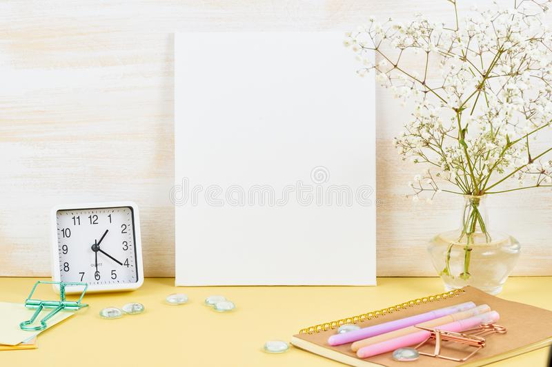 Mockup with blank white frame on yellow table against wooden wall, alarm, flower in vaze stock image