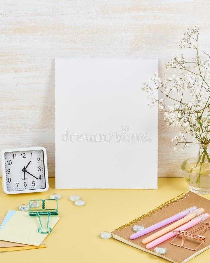 Mockup with blank white frame on yellow table against wooden wall, alarm, flower in vaze, vertical.  royalty free stock photos