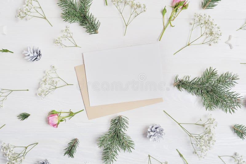 Mockup bożych narodzeń skład Kartka bożonarodzeniowa i kwiaty, sosna konusujemy, jodeł gałąź na drewnianym białym tle z miejscem fotografia stock