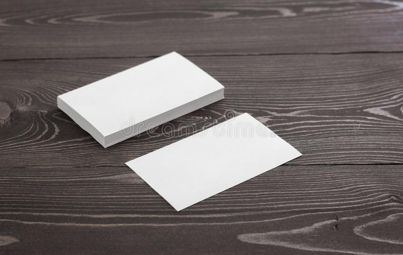 Mockup of business cards on a dark wood background. Template for branding identity. Business cards stock photo