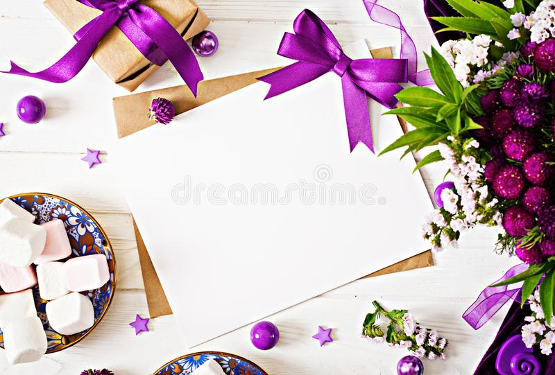 Mockup. Cards and flowers, box gift,violet ribbon and cloth lying on a white table. stock photo