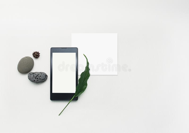 Mockup cellphone creative layout. Flat lay smartphone, blank note paper. White table background. Blank mock up paper and screen royalty free stock images