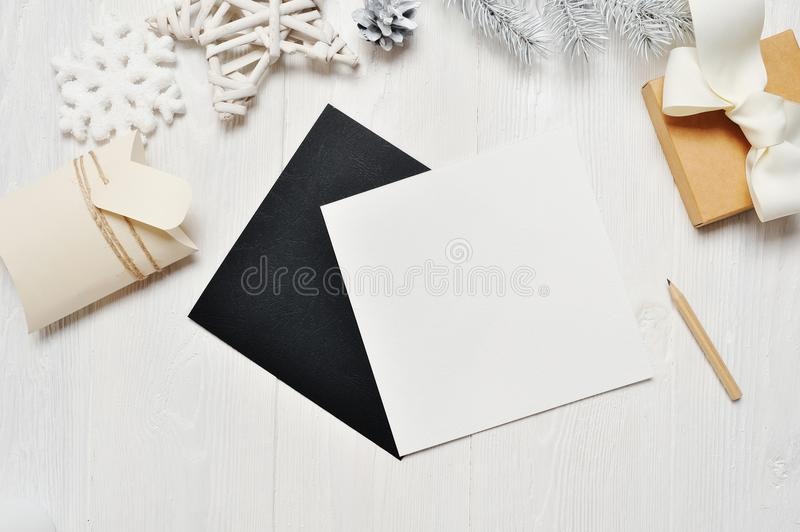 Mockup Christmas black greeting card letter in envelope and gift, flatlay on a white wooden background, with place for stock image