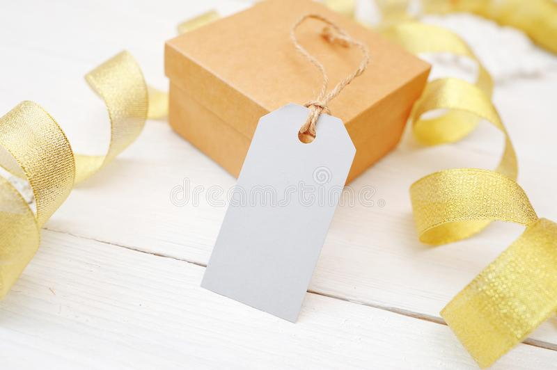 Mockup christmas gift with blank tag on white wooden background with gold ribbon royalty free stock image