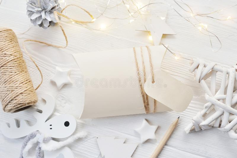 Mockup Christmas greeting card bonbonniere and tag top view, flatlay on a white wooden background with a garland stock photography