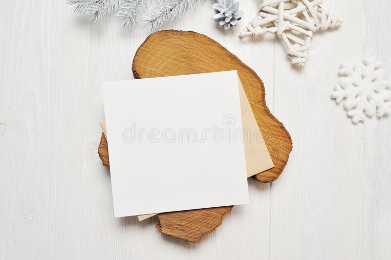 Mockup Christmas greeting card letter in envelope with white tree, flatlay on a white wooden background, with place for royalty free stock photos