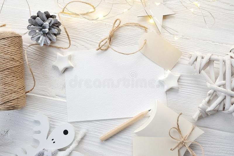 Mockup Christmas greeting card top view, flatlay on a white wooden background with a garland royalty free stock images