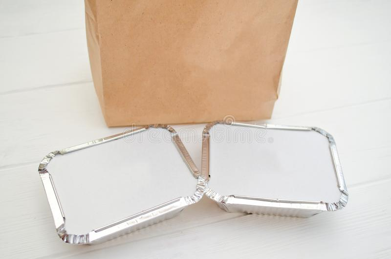 Mockup for delivery of fast food, foil plates with a cardboard cover, near a paper bag on white background royalty free stock photo