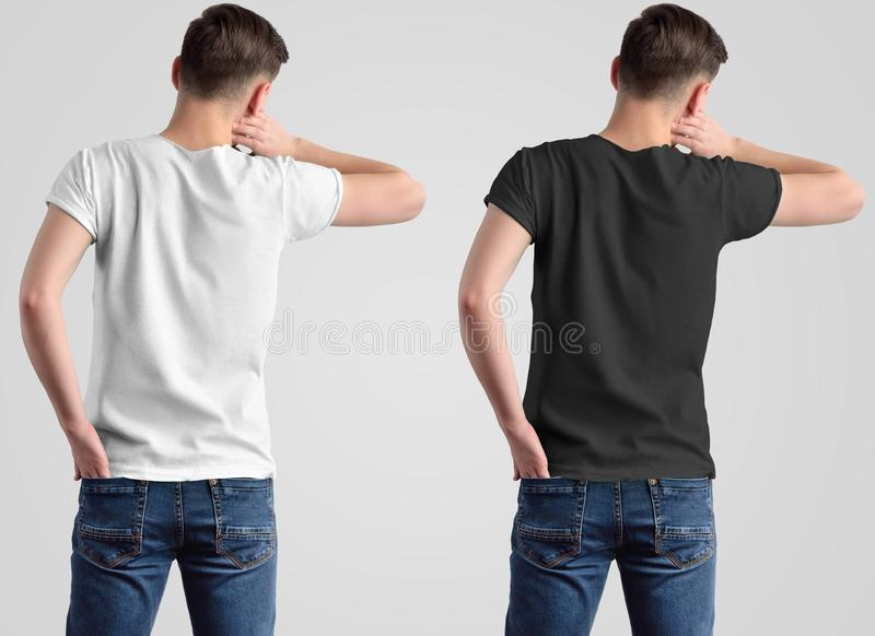 Mockup design of a white and black t-shirt on a young guy, rear view stock photo