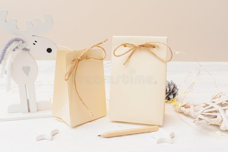 Mockup dwa bożego narodzenia Kraft prezenta pakunku z etykietką na drewnianym tle Odg?rny widok dla kartki z pozdrowieniami obraz stock