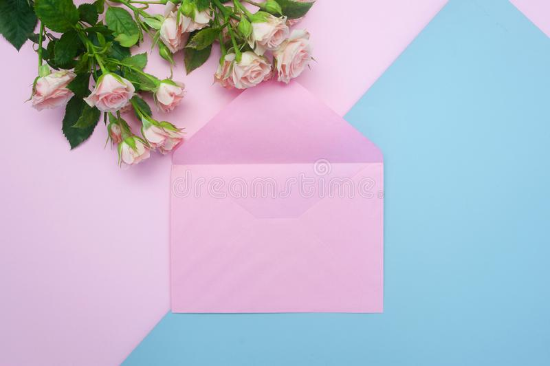 Mockup empty pink envelope and buds of pink roses, festive background, copy space.  royalty free stock photography