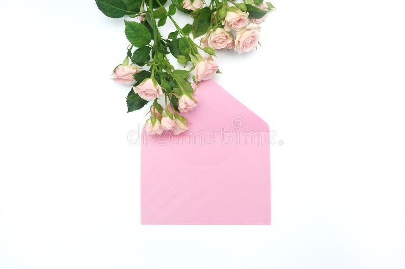 Mockup empty pink envelope and buds of pink roses with place for text, festive white background, copy space.  stock photography