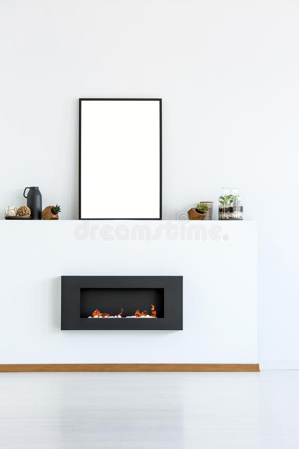 Mockup of empty poster above black fireplace in simple white living room interior. Real photo. With a place for your graphic royalty free stock images