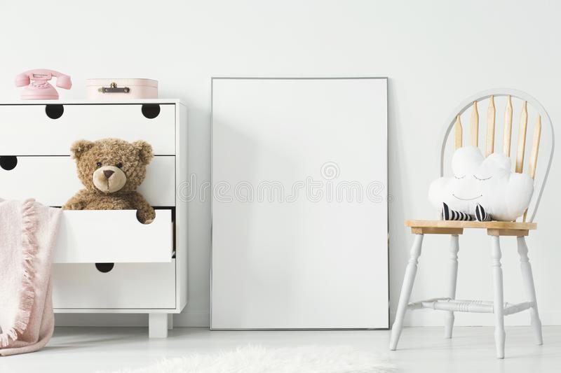 Mockup of empty poster and cabinet with plush toy and pink blank. Et in white child`s room interior. Real photo with a place for your graphic royalty free stock photography