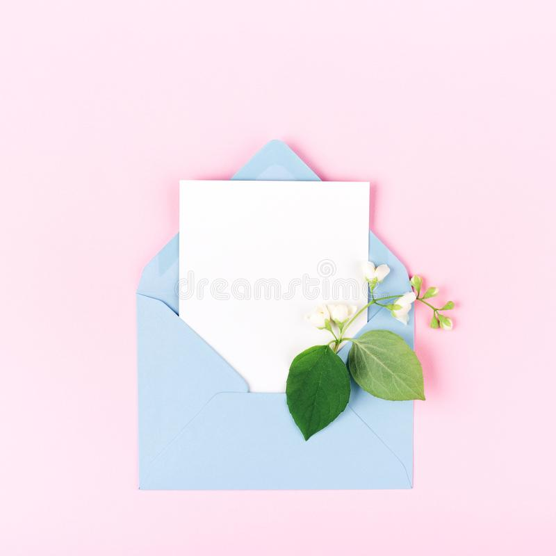 Mockup with envelope and flower on pink background. Mockup with blue envelope and jasmine flower on pink background. Minimal styled flat lay in pastel colors royalty free stock photo