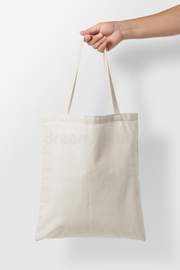 Mockup of female hand holding a blank Tote Canvas Bag on light grey background. royalty free stock image