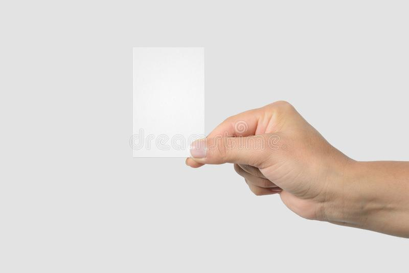 Mockup of female hand holding a Business Card on light grey background. Size 85x 55 mm stock photography
