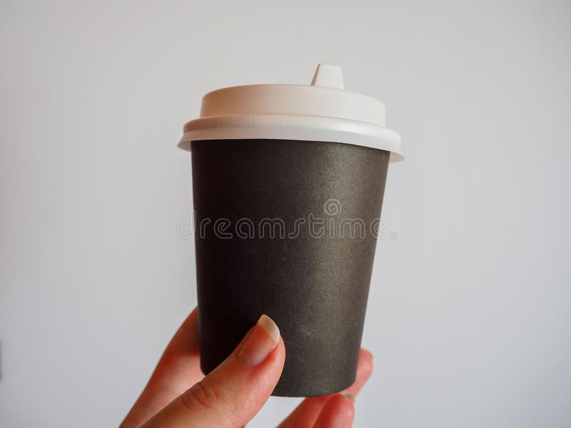Mockup of female hand holding a coffee paper takeaway cup on grey background with copy space stock image