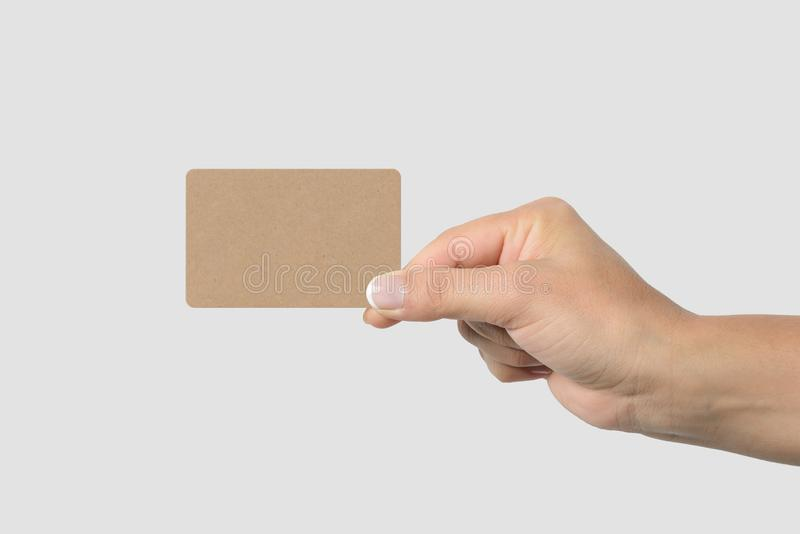 Mockup of female hand holding a Kraft Paper Business Card on light grey background. royalty free stock photo