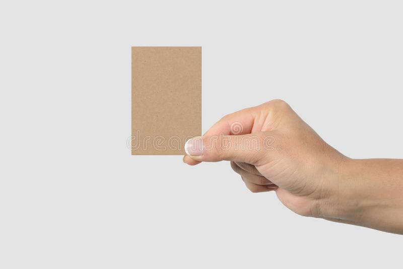 Mockup of female hand holding a Kraft Paper Business Card on light grey background. royalty free stock photography
