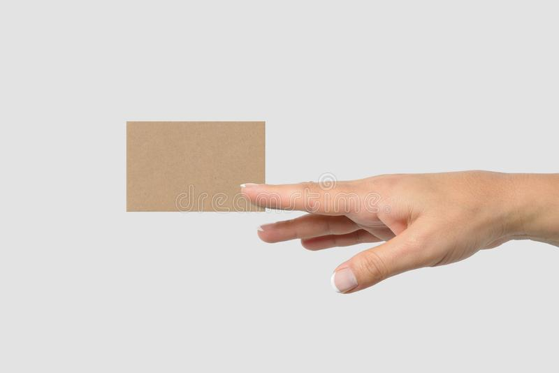 Mockup of female hand holding a Kraft Paper Business Card on light grey background. stock images