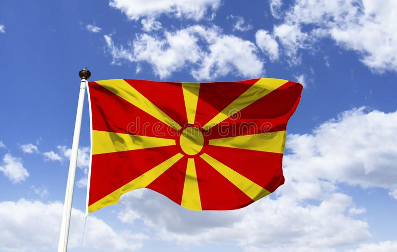 Mockup of the flag of Northern Macedonia. Floating under a blue sky. Country located on the Balkan peninsula in southeastern Europe. Motto: Freedom or Death stock photography