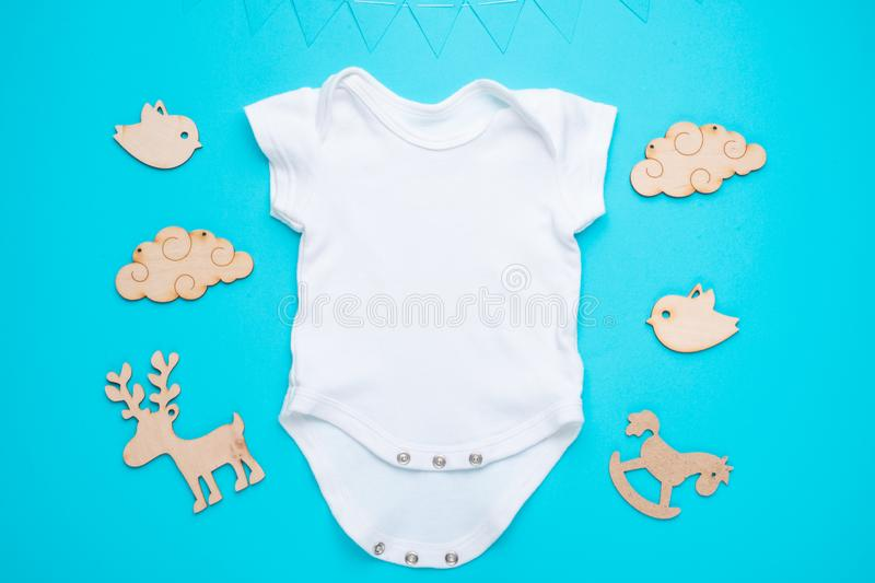 Mockup Flat Lay a white baby shirt with wooden toys on a blue background. Layout for the design and placement of logos,. Advertising, children`s party baby stock photography