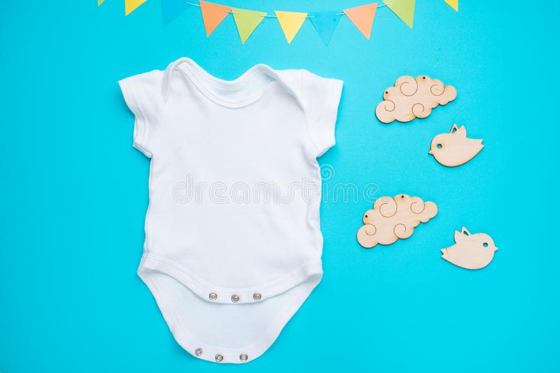 Mockup Flat Lay a white baby shirt with wooden toys on a blue background. Layout for the design and placement of logos,. Advertising, children`s party baby stock photos
