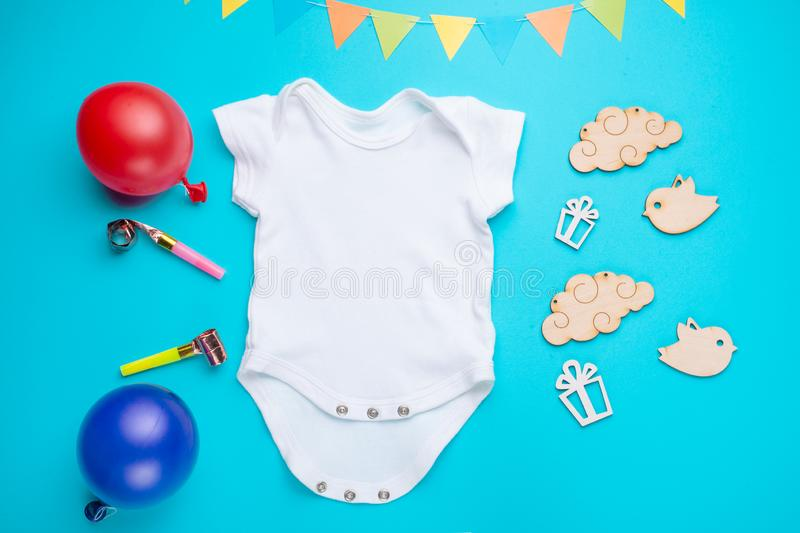 Mockup Flat Lay white children shirt with toys and balls on a blue background. Layout for the design and placement of logos,. Advertising, children`s party baby royalty free stock photos