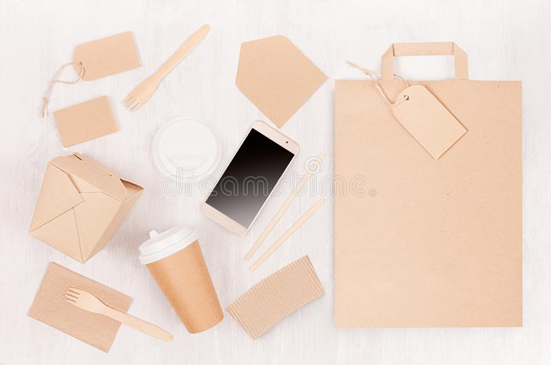 Mockup food takeaway packaging for cafe and restaurant - phone, bag, cardboard box for coffee, noodles on light white wood table. Mockup food takeaway packaging stock image
