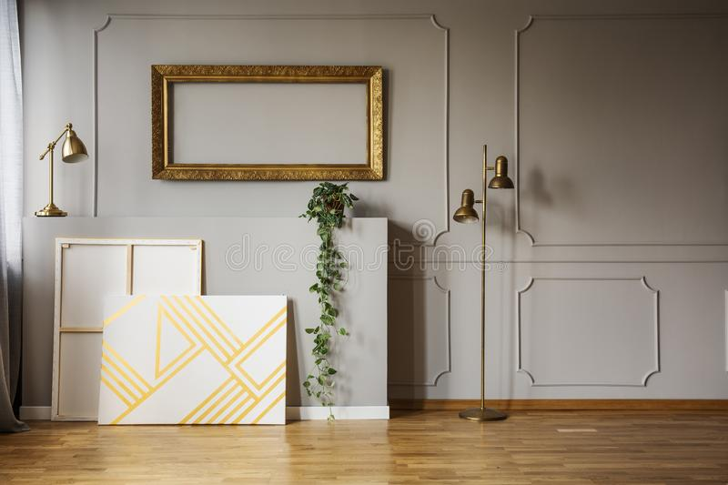 Mockup of gold frame above paintings in grey loft interior with lamps and plant. Real photo royalty free stock photos