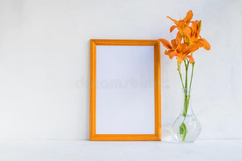 Mockup with a golden frame and orange summer flowers royalty free stock photo
