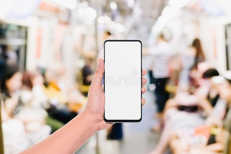 Mockup of hand using mobile phone with copy space blank screen for your advertisement with blurred view of people in public train royalty free stock photos
