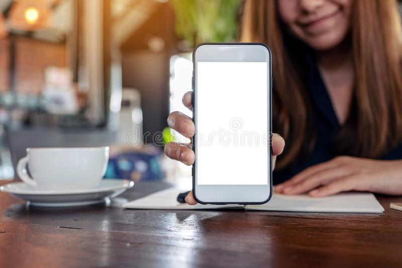 Mockup image of an asian woman holding and showing white mobile phone with blank desktop screen with coffee cups. And notebooks on vintage wooden table in cafe stock image