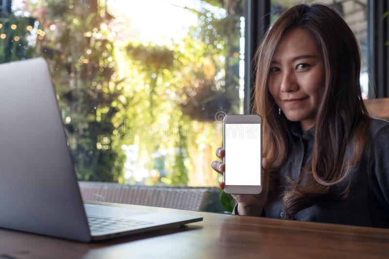 Mockup image of a beautiful Asian business woman holding and showing white mobile phone with blank screen with laptop on wooden ta royalty free stock photos