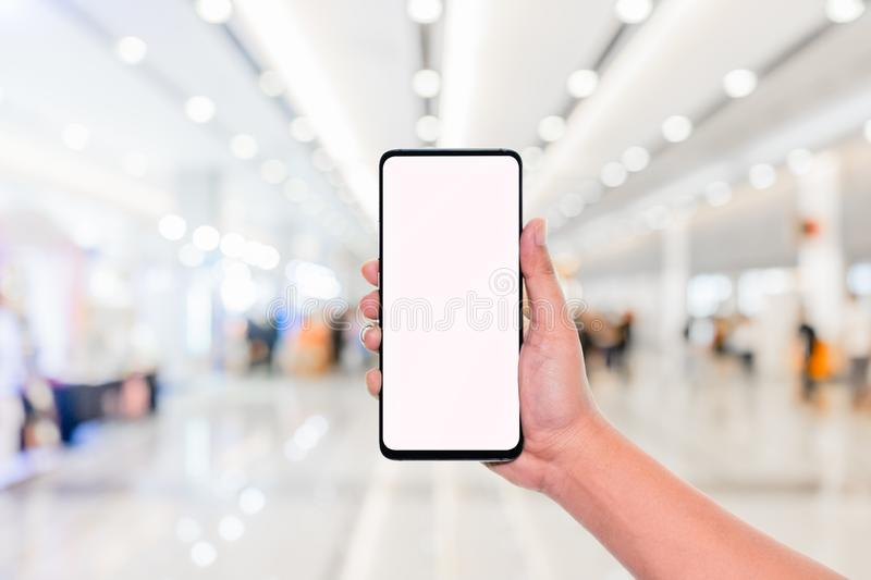 Mockup image of hand holding mobile phone with blank white screen with blur office corridor hall way background bokeh light,White stock photo