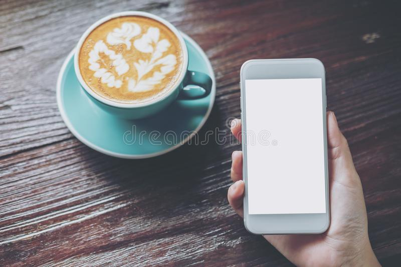 Mockup image of hand holding white mobile phone with blank screen with blue hot coffee cup on vintage wooden table. In restaurant stock image