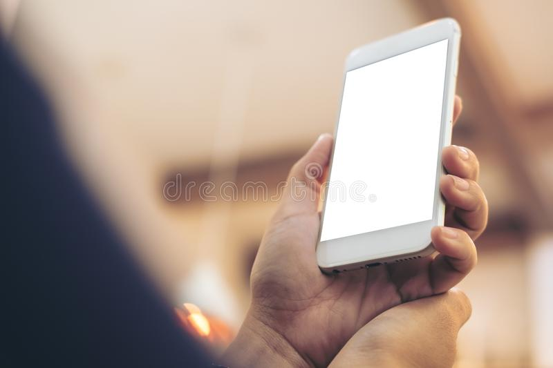 Mockup image of hands holding and raising white mobile phone with blank screen stock photography