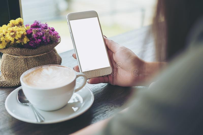 Hands holding white mobile phone with blank white screen with hot coffee cup and flower vase in cafe. Mockup image of hands holding white mobile phone with blank royalty free stock image