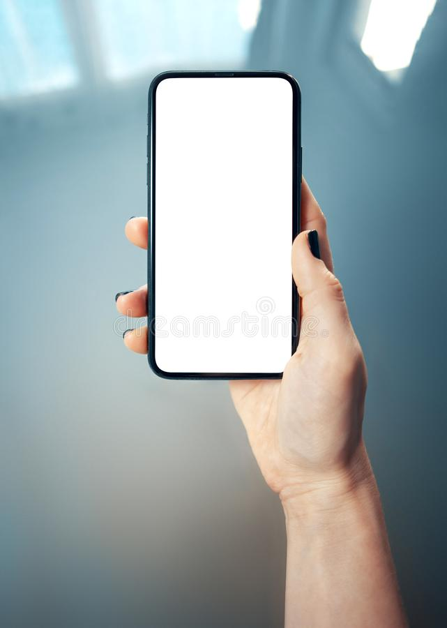Free Mockup Image Of Woman`s Hand Holding Thin Bezels Mobile Phone With Blank Screen In Glossy And Blurry Corporate Environment - Imag Stock Images - 163739114