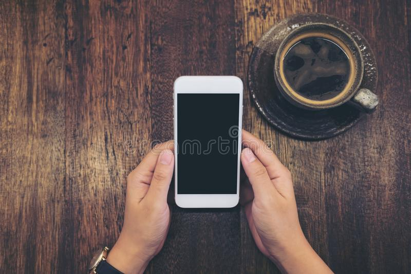 Mockup image of white mobile phone with blank black screen and hot coffee cup on vintage wood table background. In cafe stock images
